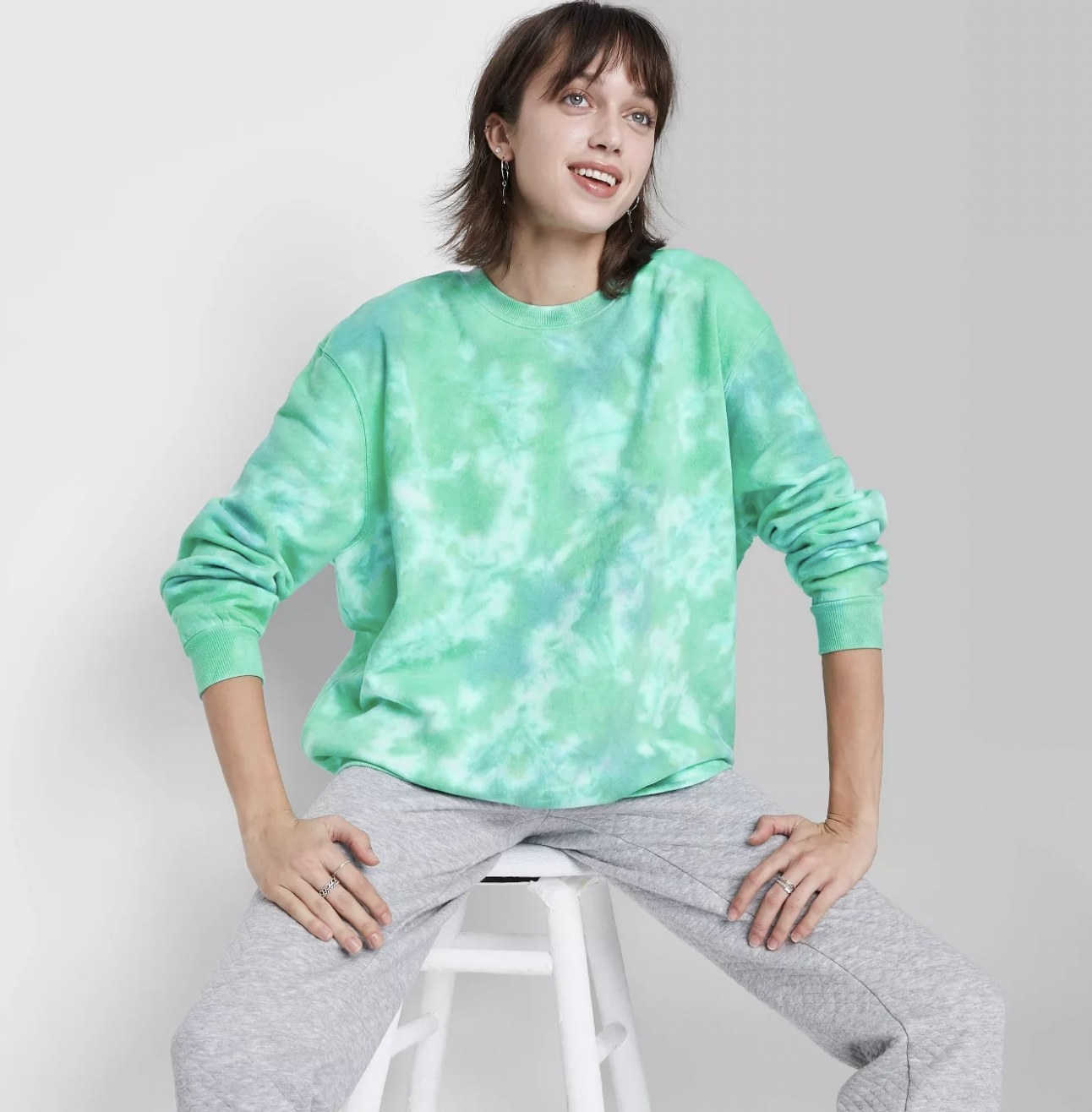 A model wearing a green and blue tie-dyed sweatshirt