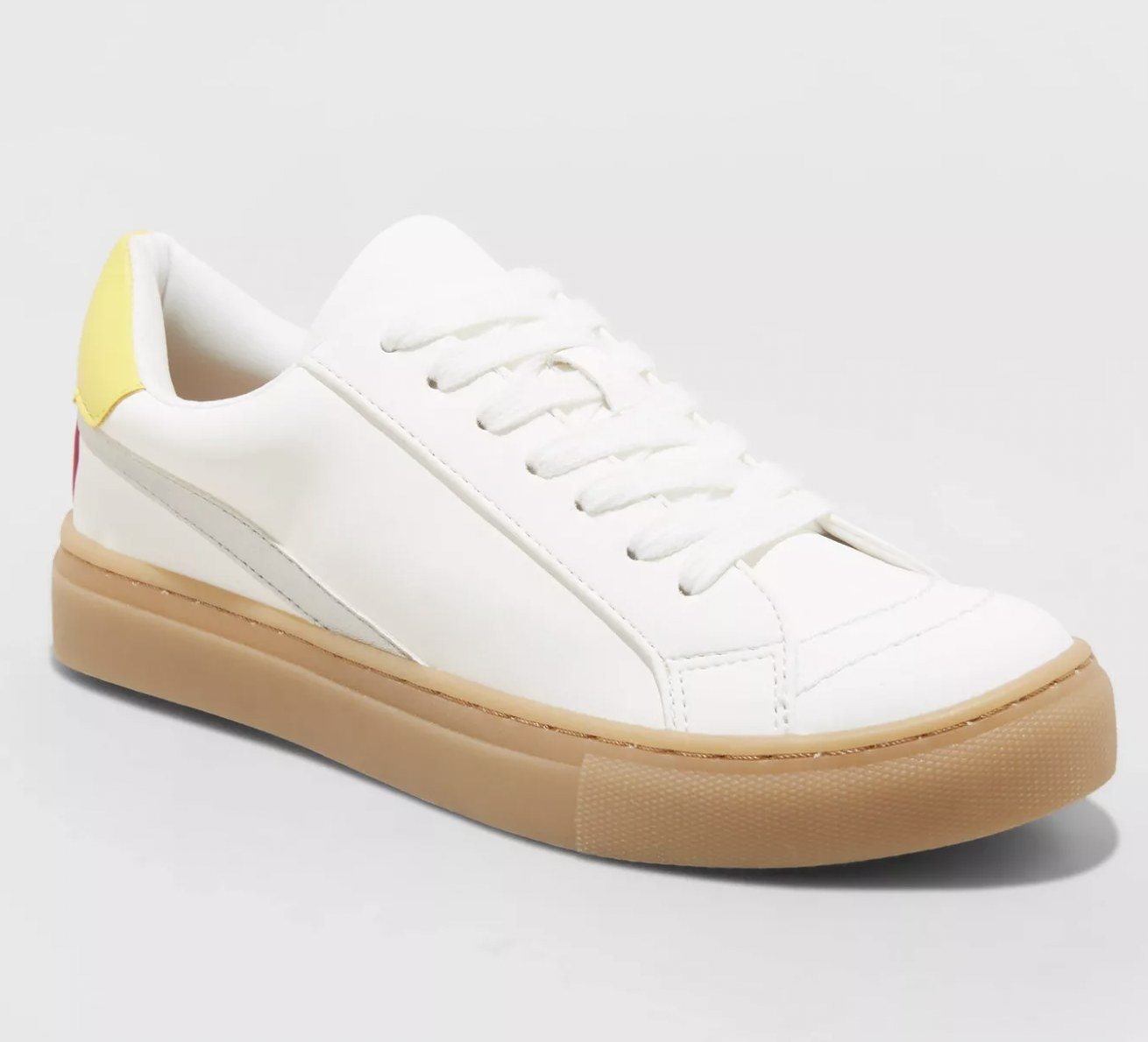 A pair of white lace-up closed toe sneakers with brown soles and a strip of yellow.
