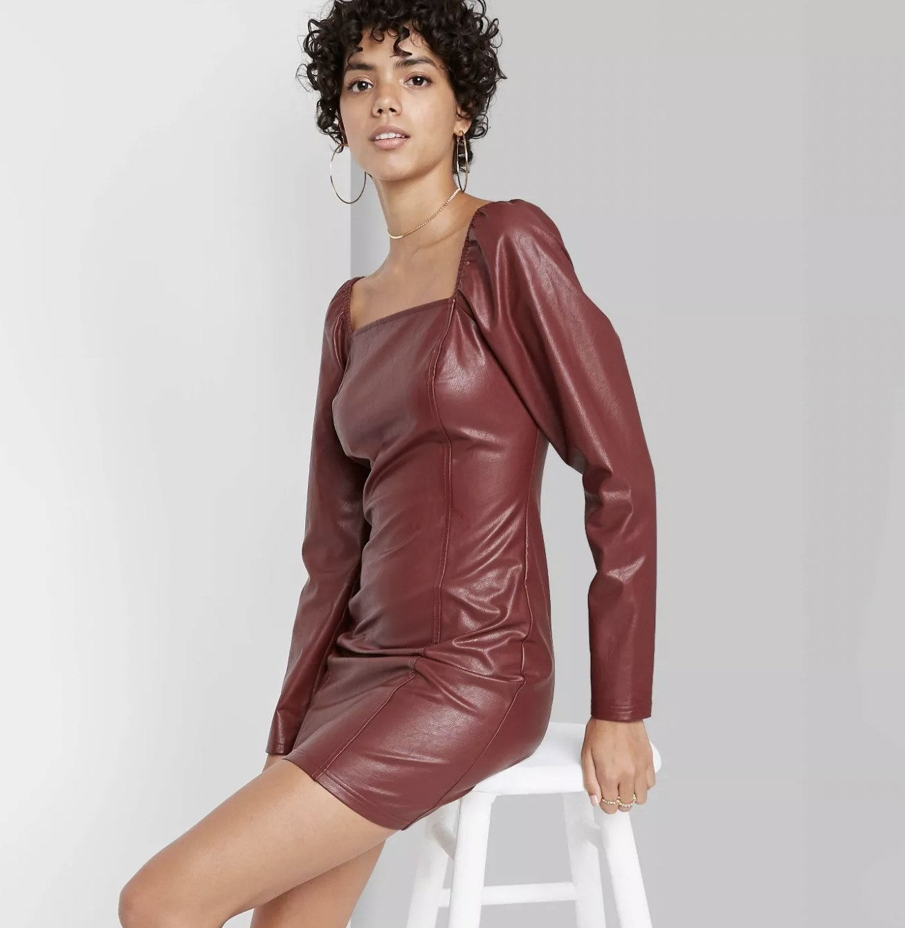 A model wearing a burgundy leather dress and hoop style earrings