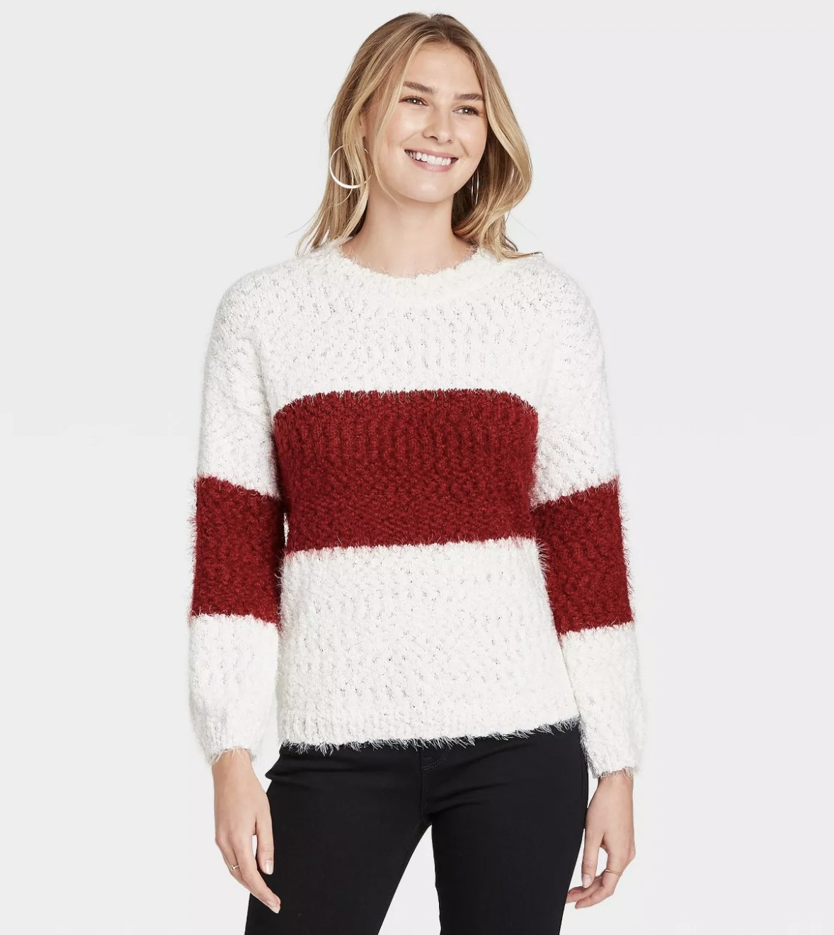 A model wearing a crimson and white sweater