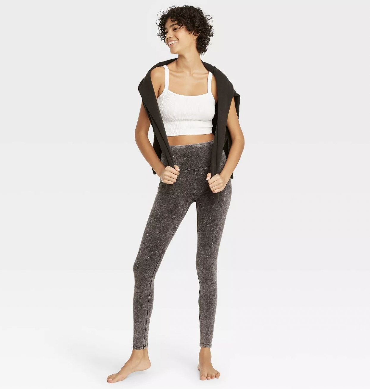 A model wearing black stonewashed leggings with a white tank top and black sweater