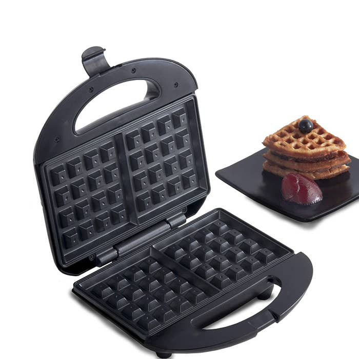 A waffle maker with waffles beside it on a plate