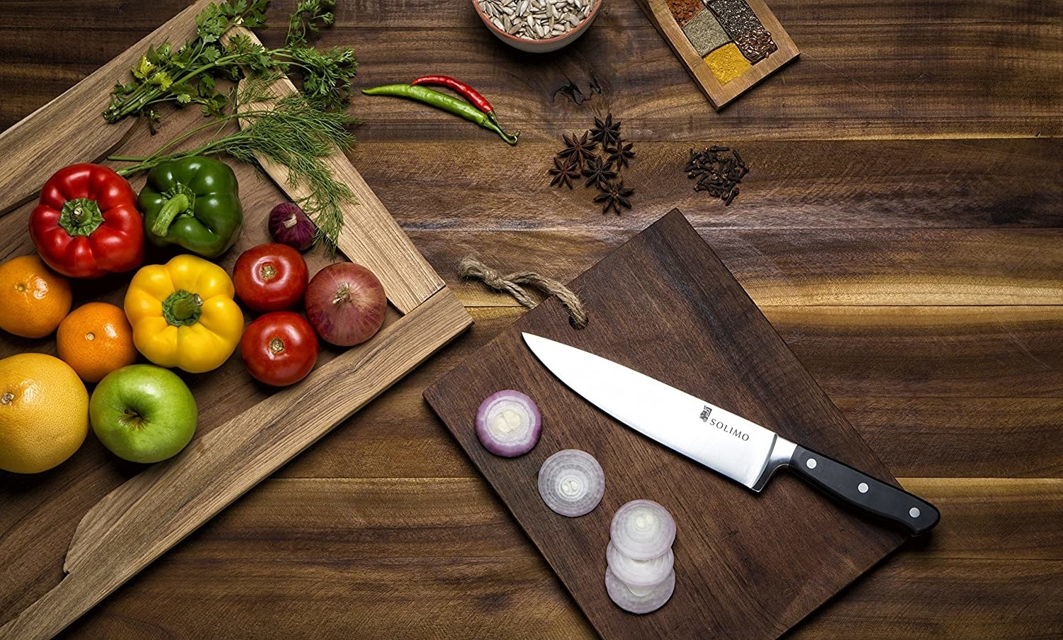A chef's knife with vegetables around it