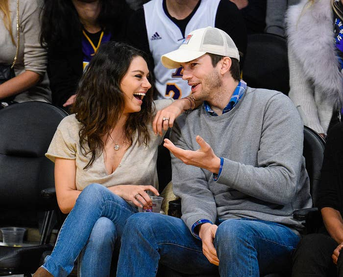 Mila Kunis and Ashton Kutcher sitting and laughing at a basketball game between the Oklahoma City Thunder and the Los Angeles Lakers