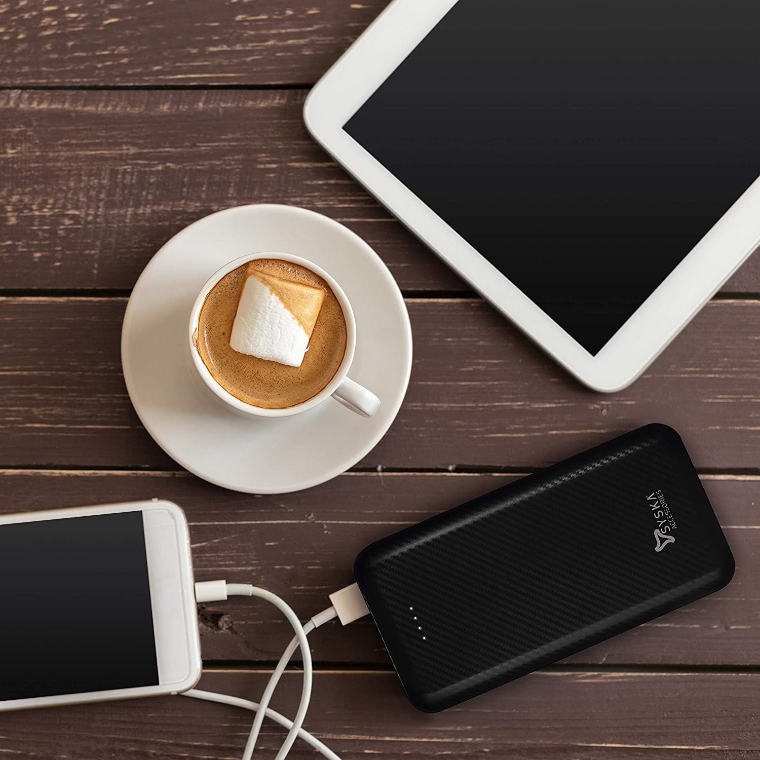 A phone connected to the powerbank, kept on a table beside a tablet and coffee.