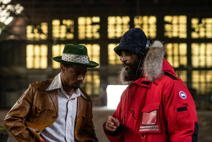 LaKeith Stanfield as William O'Neal wearing a greed fedora and tan leather jacket with Shaka King giving him directions on set