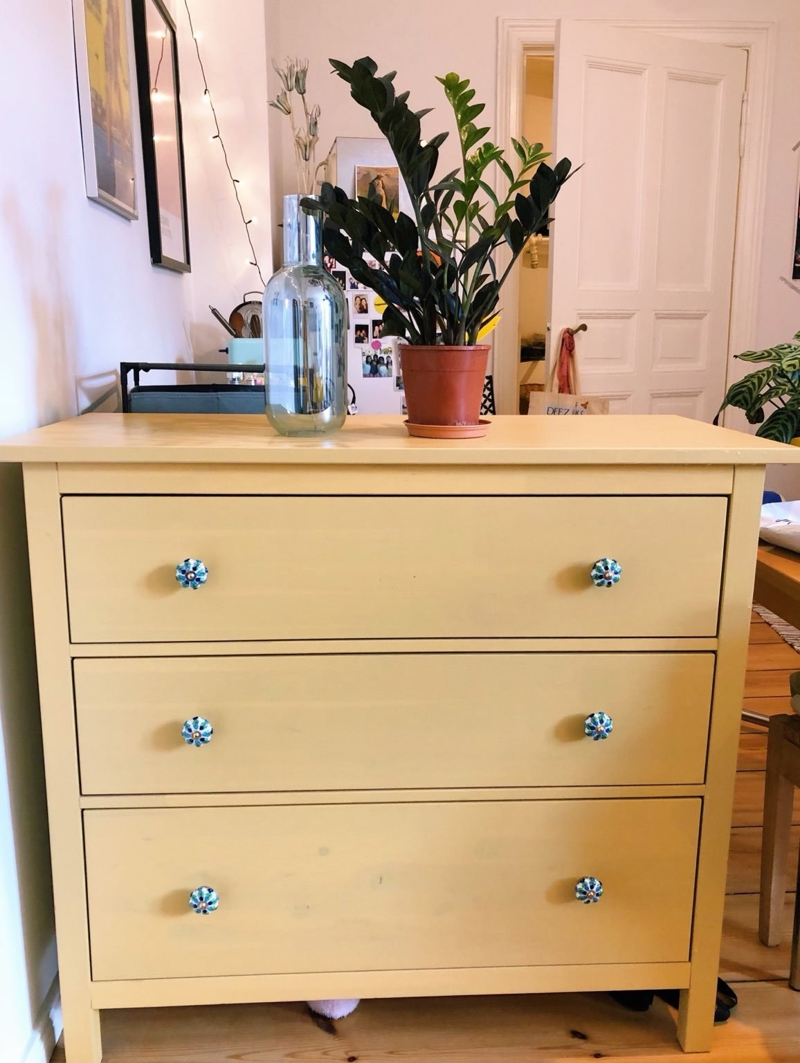 Bright yellow chest of drawers with blue and white knobs in writer's bedroom