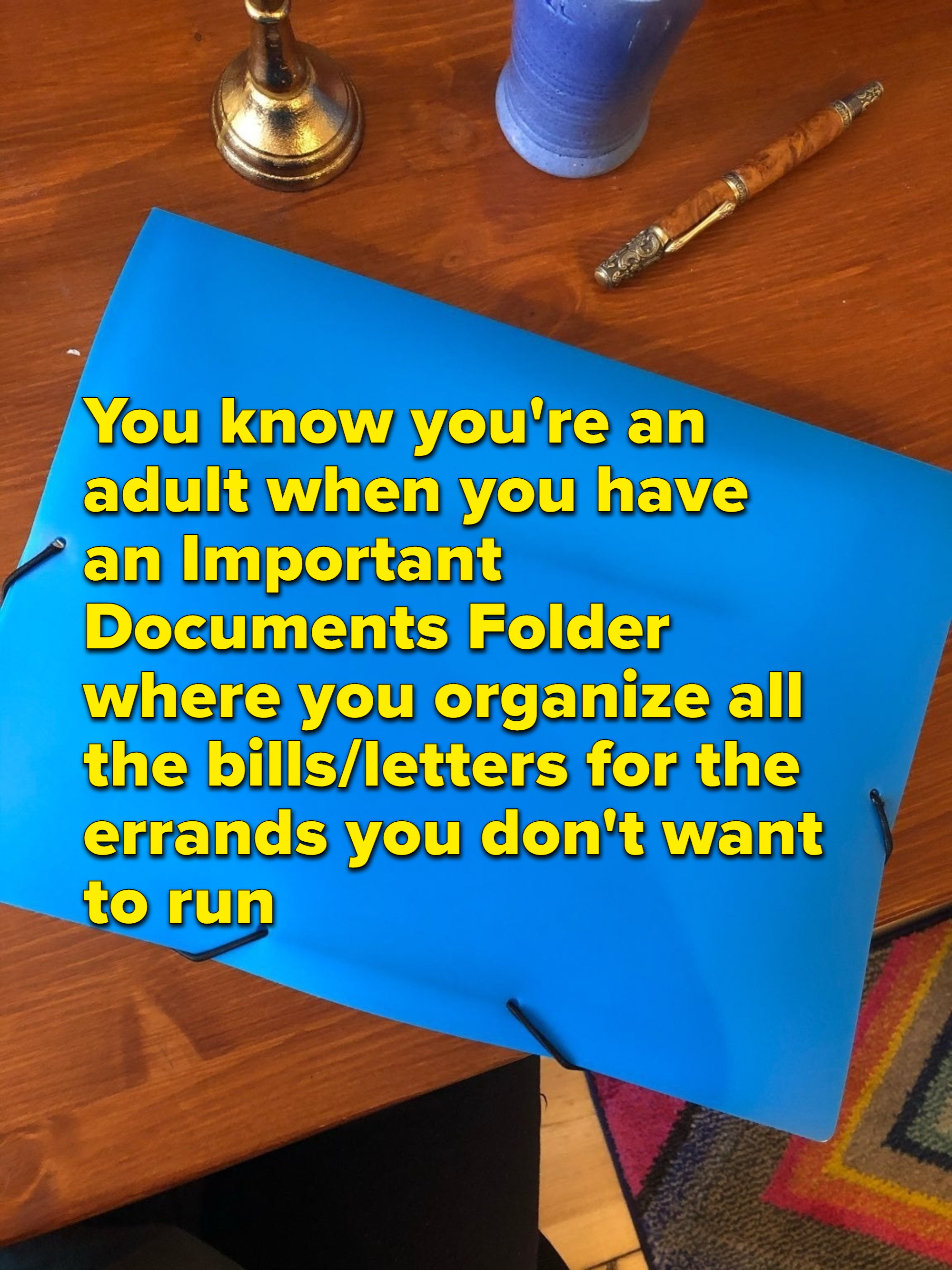 "Bright blue folder on a wooden desk, with text overlay reading, ""You know you're an adult when you have an Important Documents folder where you organize all the bills and letters for the errands you don't want to run"""