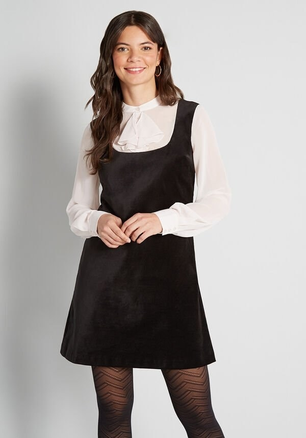 Model wearing mini dress with white ruffle collar and sleeves and black velvet shift bodice