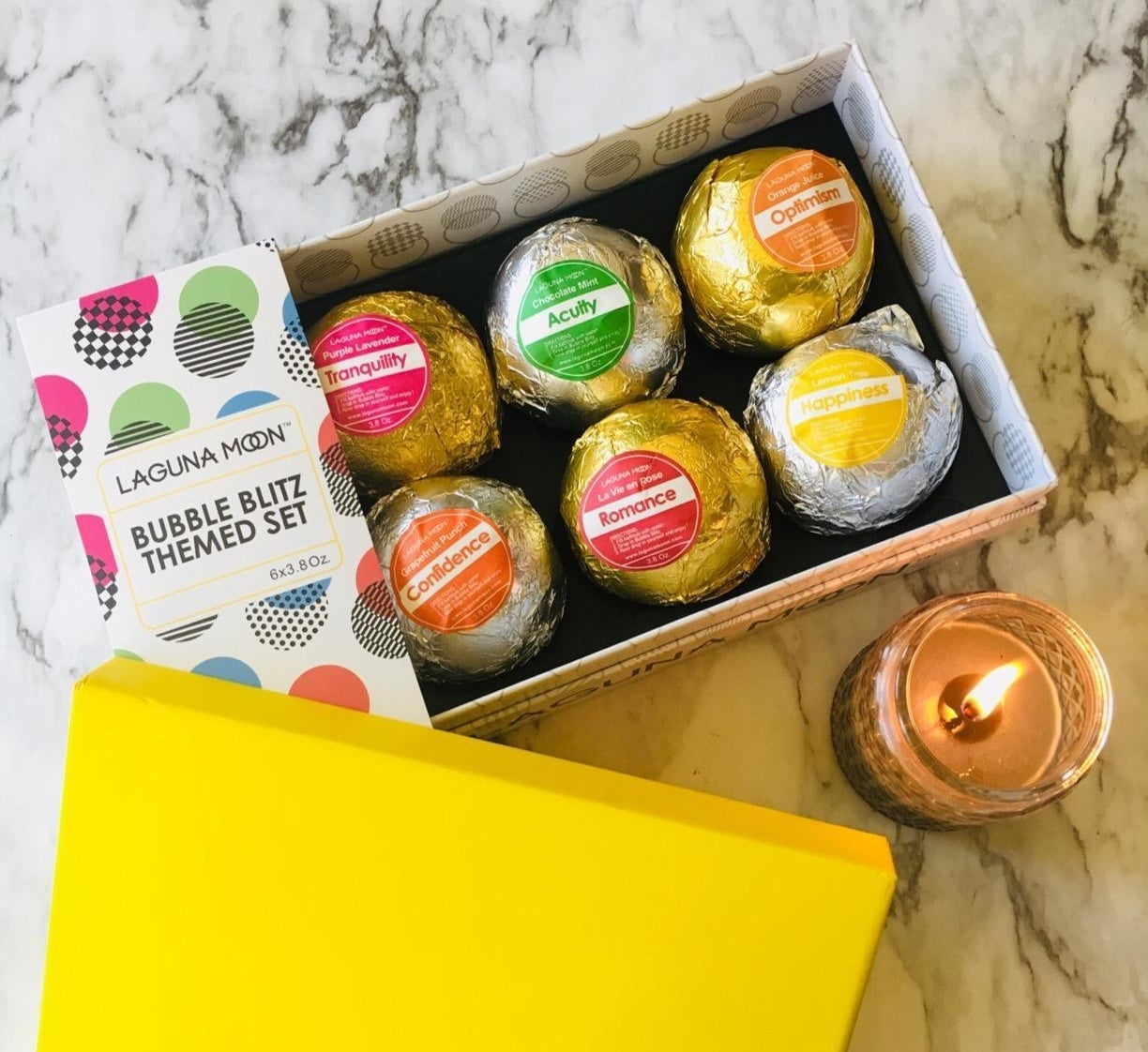 reviewer image of the lagunamoon bath bombs in their box packaging next to a lit candle