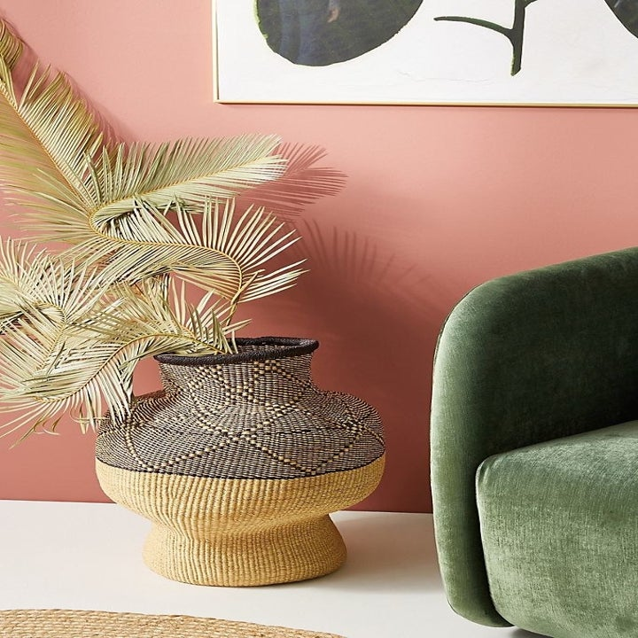 woven patterned vase with pampas grass next to velvet green couch