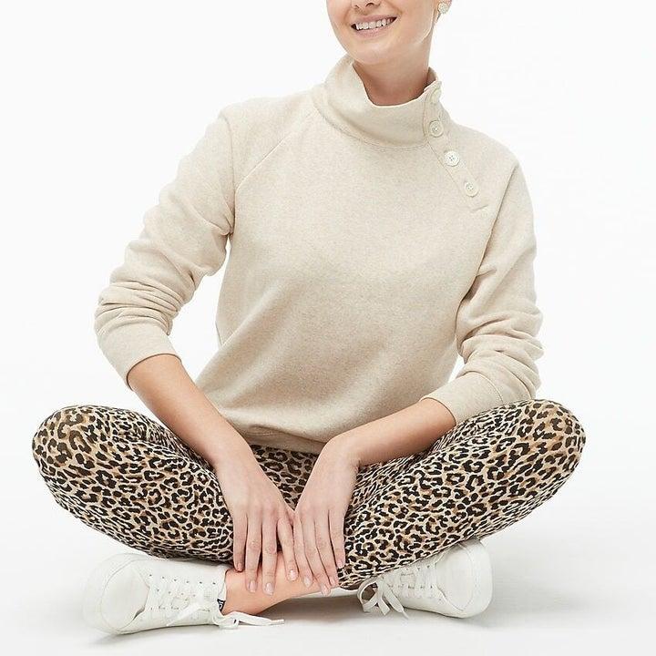 Model wears oatmeal colored sweater with leopard print leggings