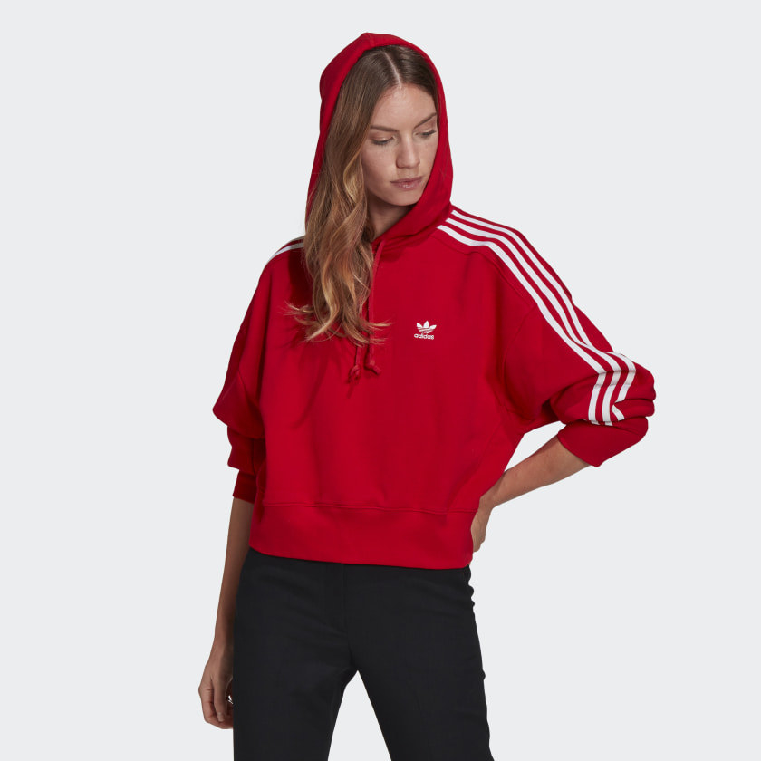 person wearing a red cropped hoodie with stripes down the arm