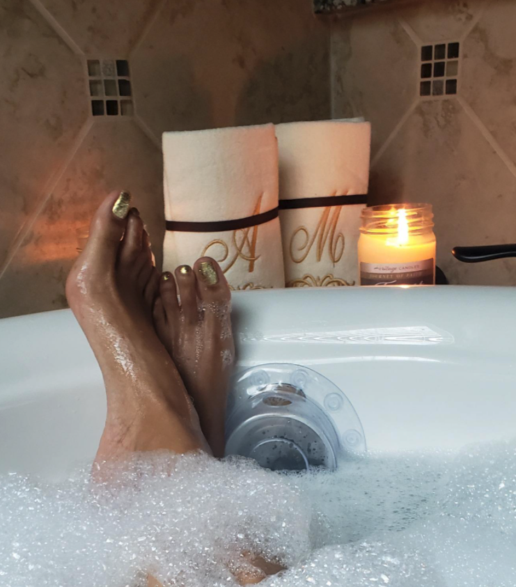 reviewer in tub filled up high with water and bubbles