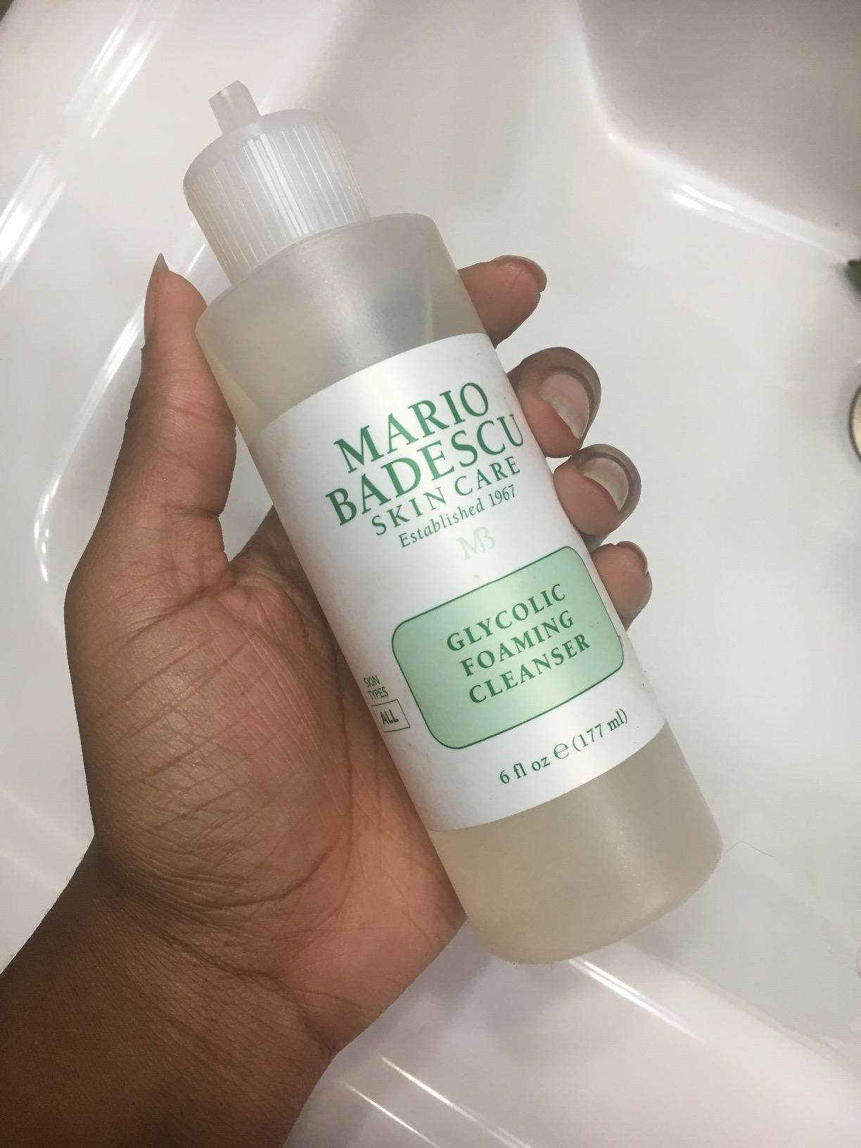 reviewer holding the cleanser bottle