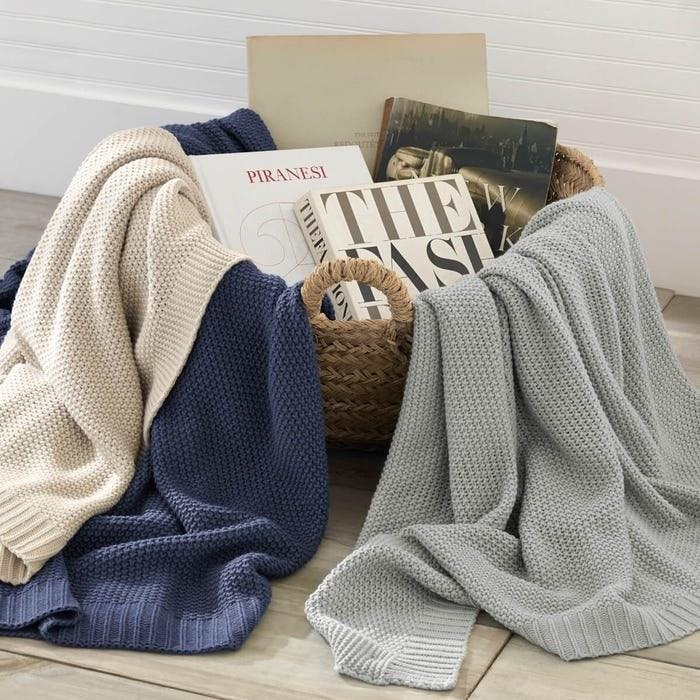 three knit throw blankets in a basket