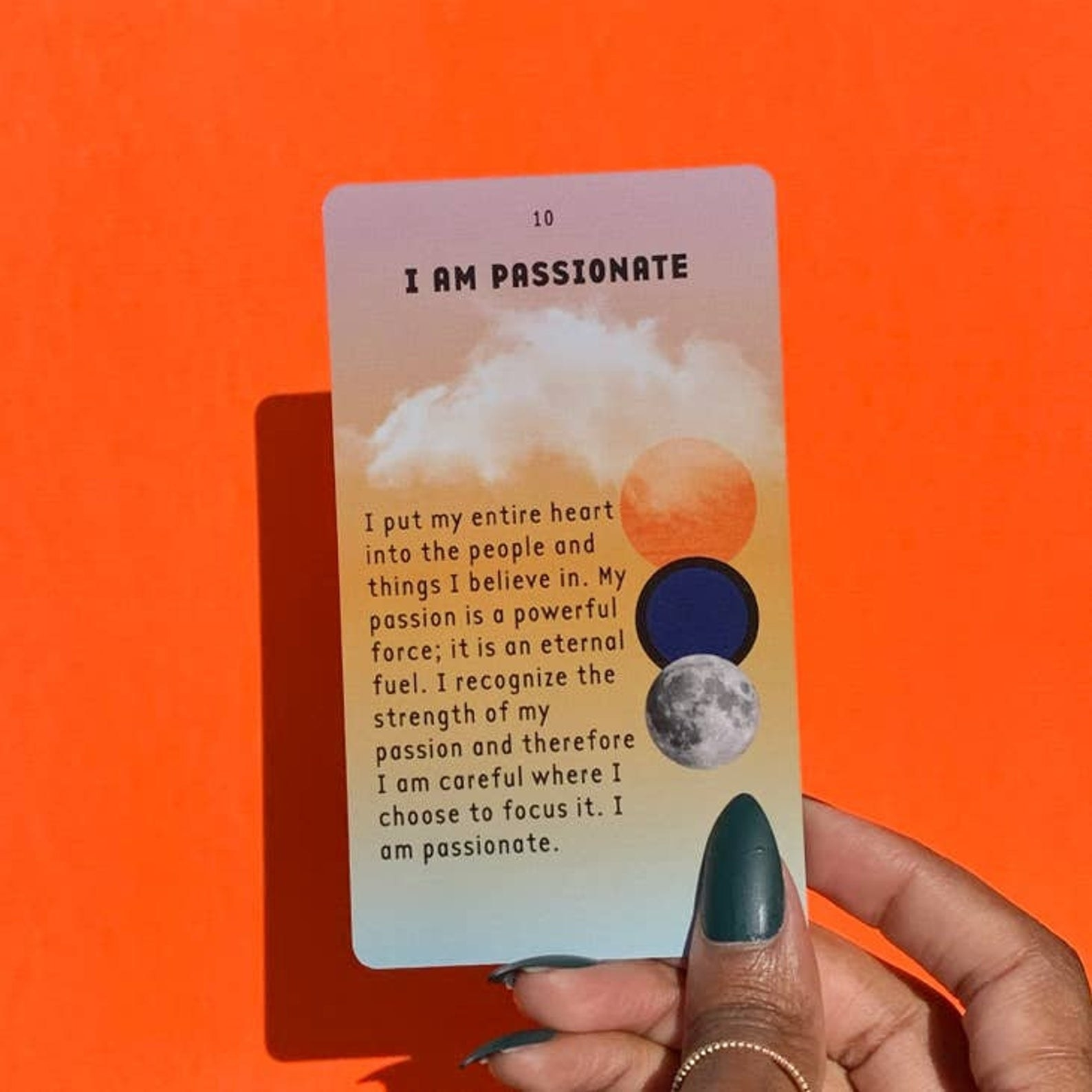 """a hand holding an affirmation card called """"i am passionate"""""""
