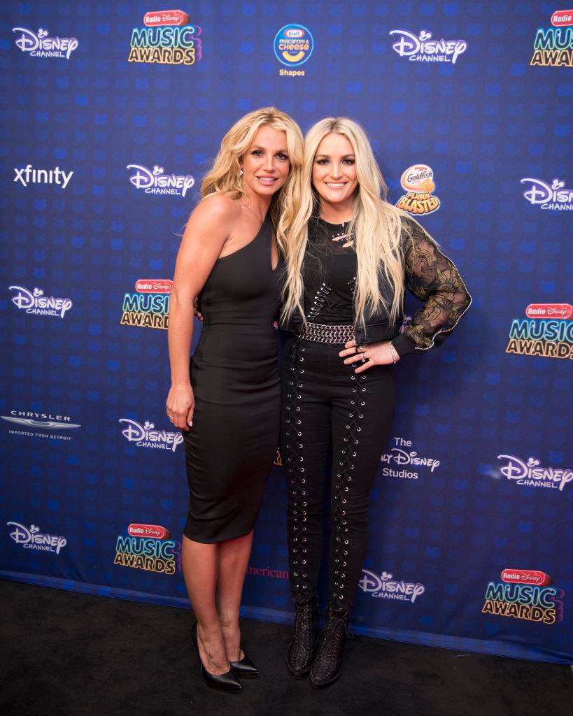 Britney, wearing a one-shouldered dress, and Jamie Lynn, wearing laced pants and a ripped top, posing at the Radio Disney Music Awards