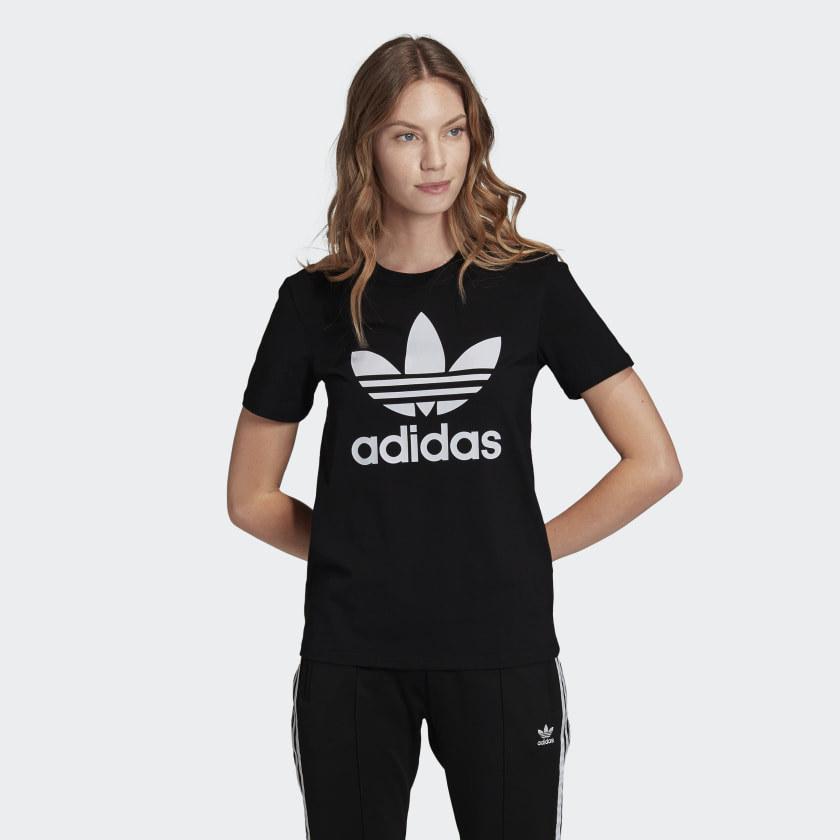 person wearing a black trefoil t-shirt