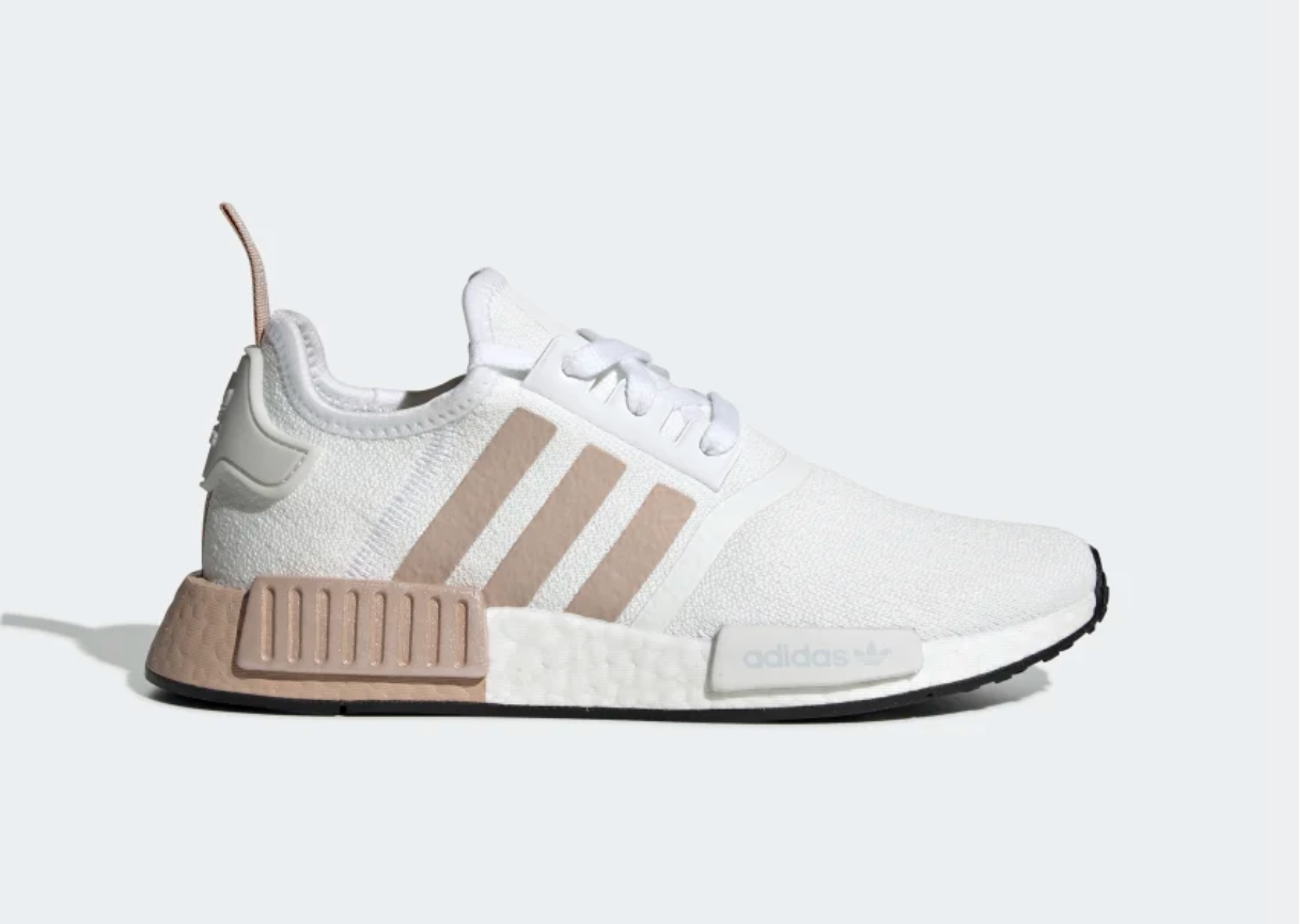 A pair of lace up white sneakers with blush pink soles and side stripes
