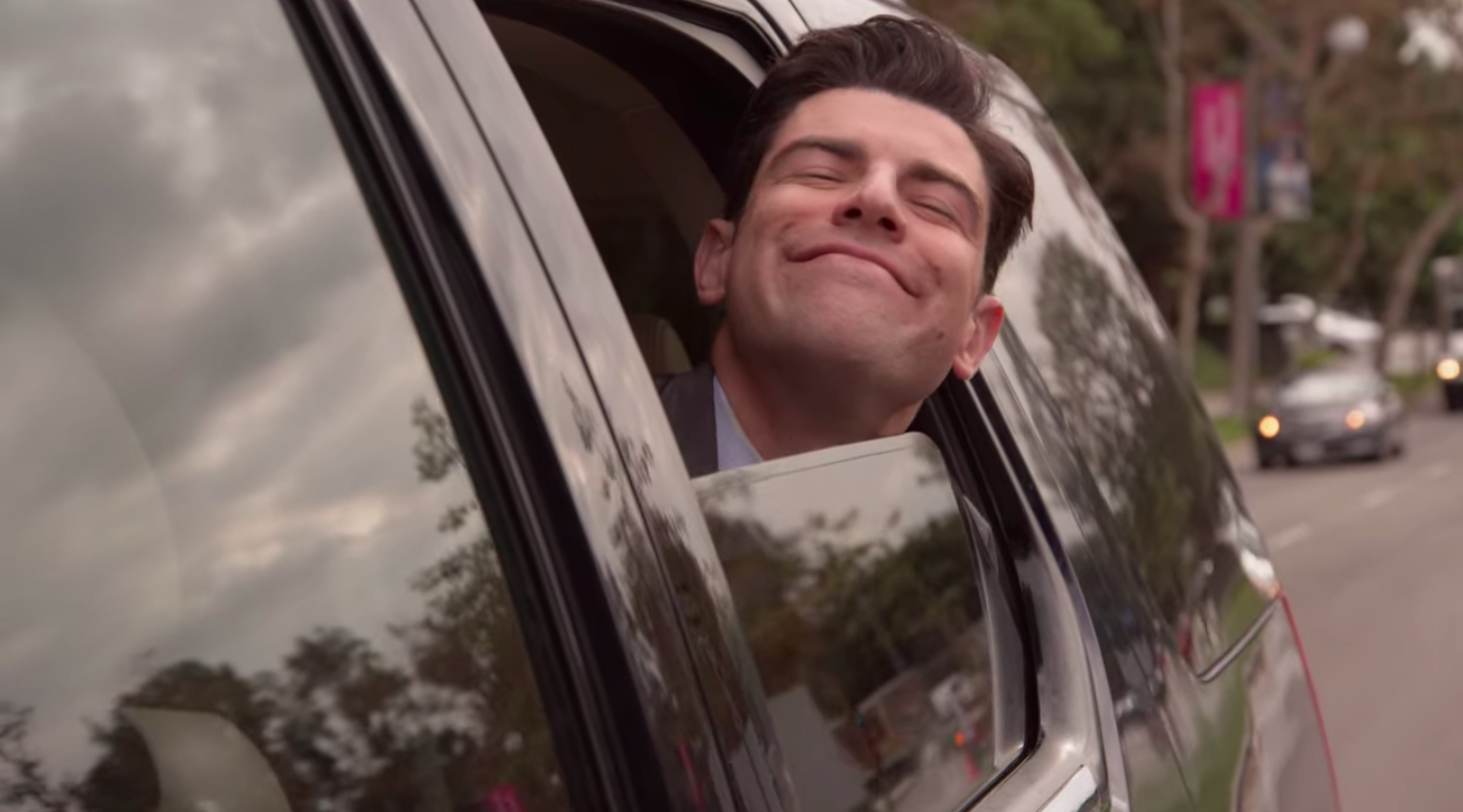 "Schmidt from ""New Girl"" smiling with his head out of a car window"