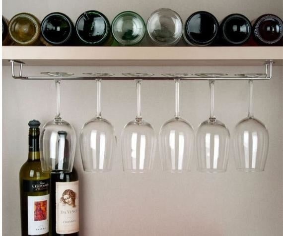 A stainless steel wine racked installed under a shelf filled with wine glasses