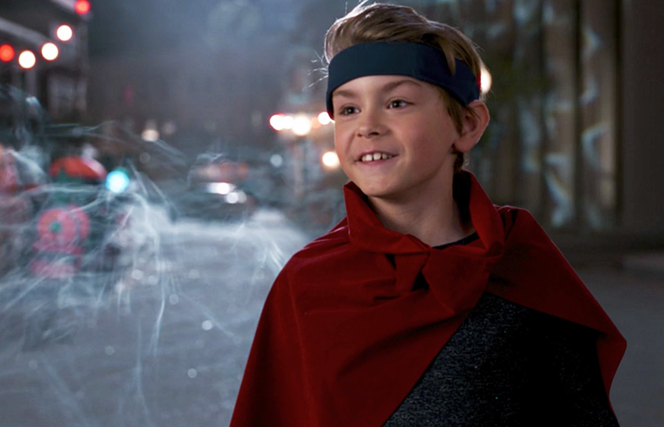 Billy's costume includes a red cape and a blue headband that circles his forehead