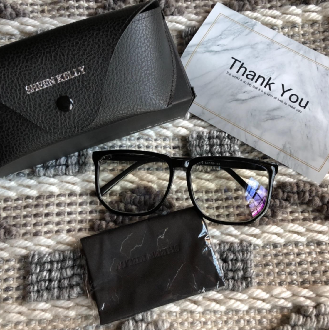 A reviewer's blue light glasses, the case, a wipe, and a thank you note