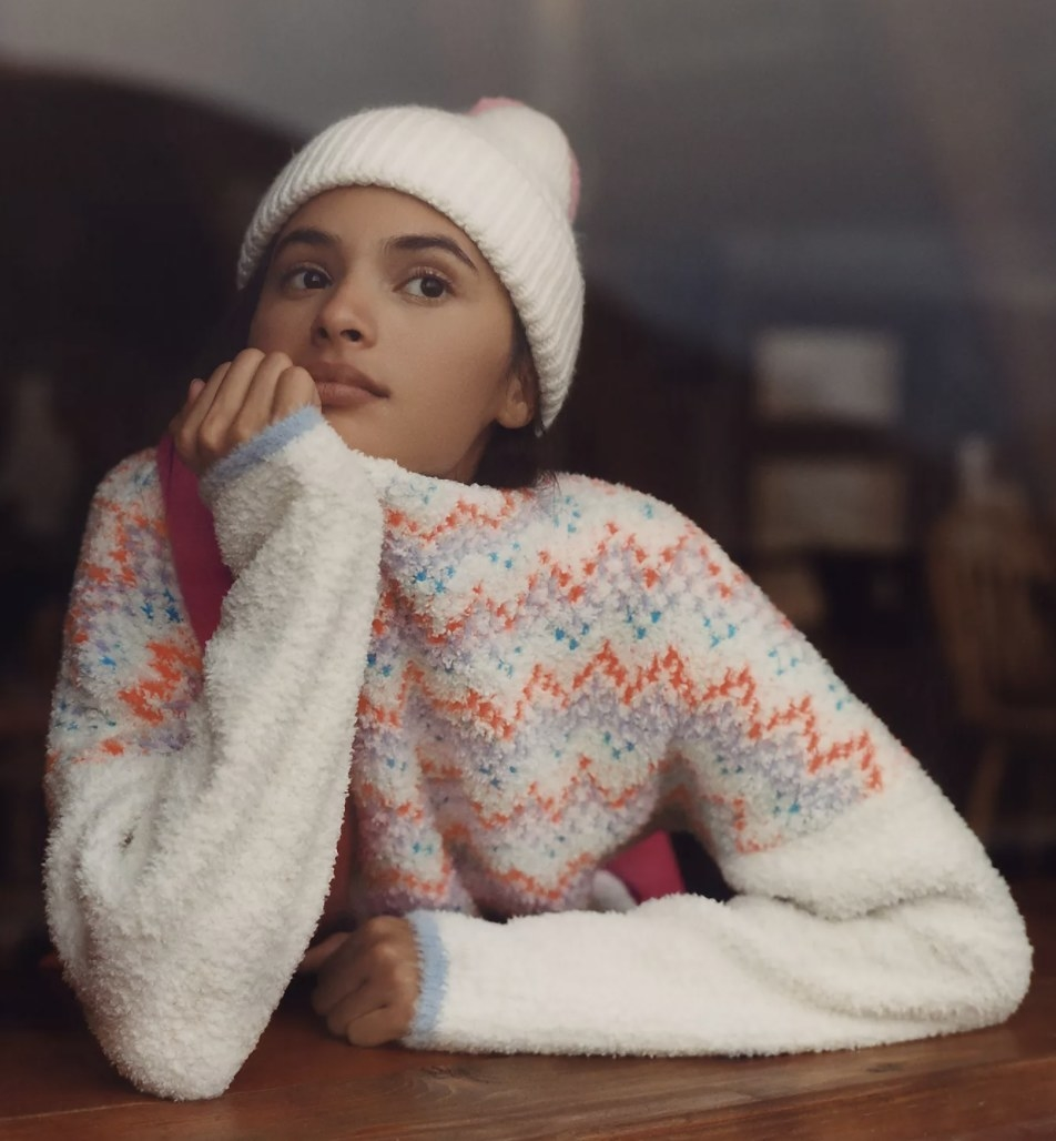 Model is wearing a white sweater with zig-zag stripes