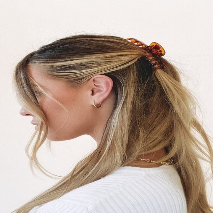 Model using the clip to wear their hair half up