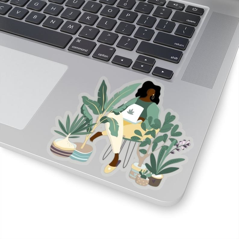 Sticker of a black woman sitting on a stool surrounded by plants