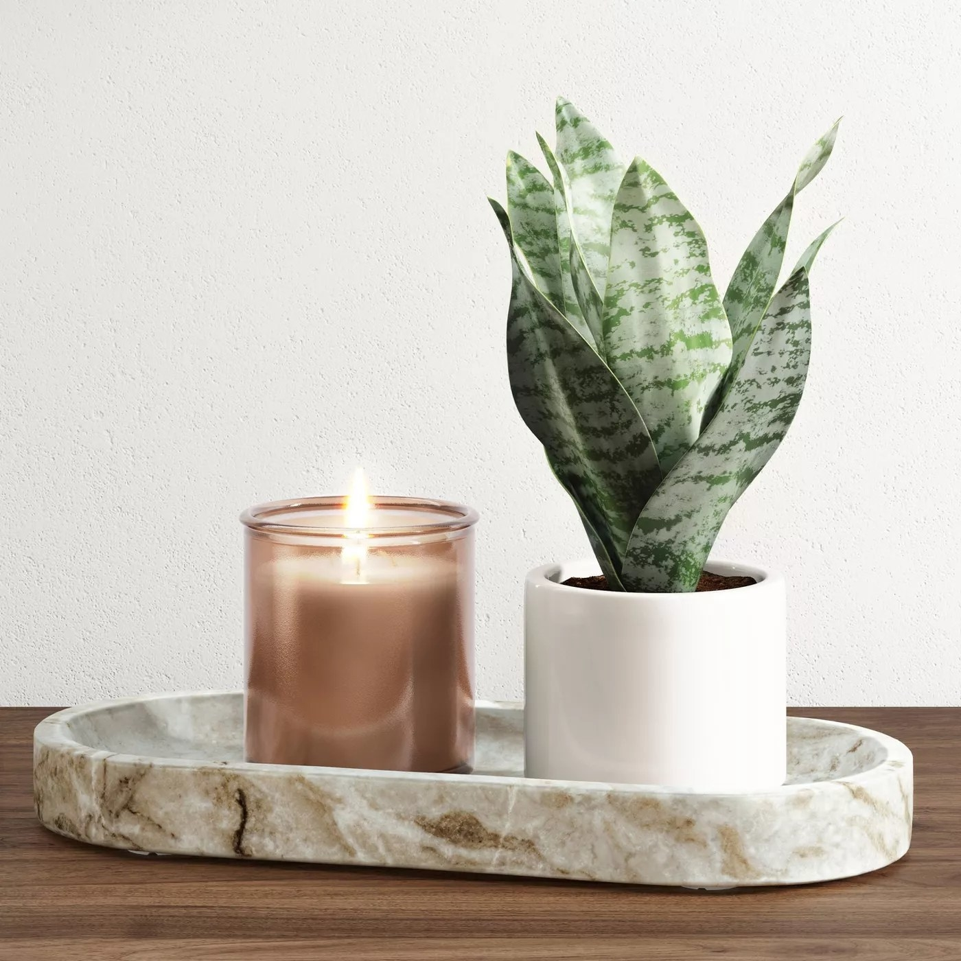 The marble tray holding a small potted plant and a lit candle