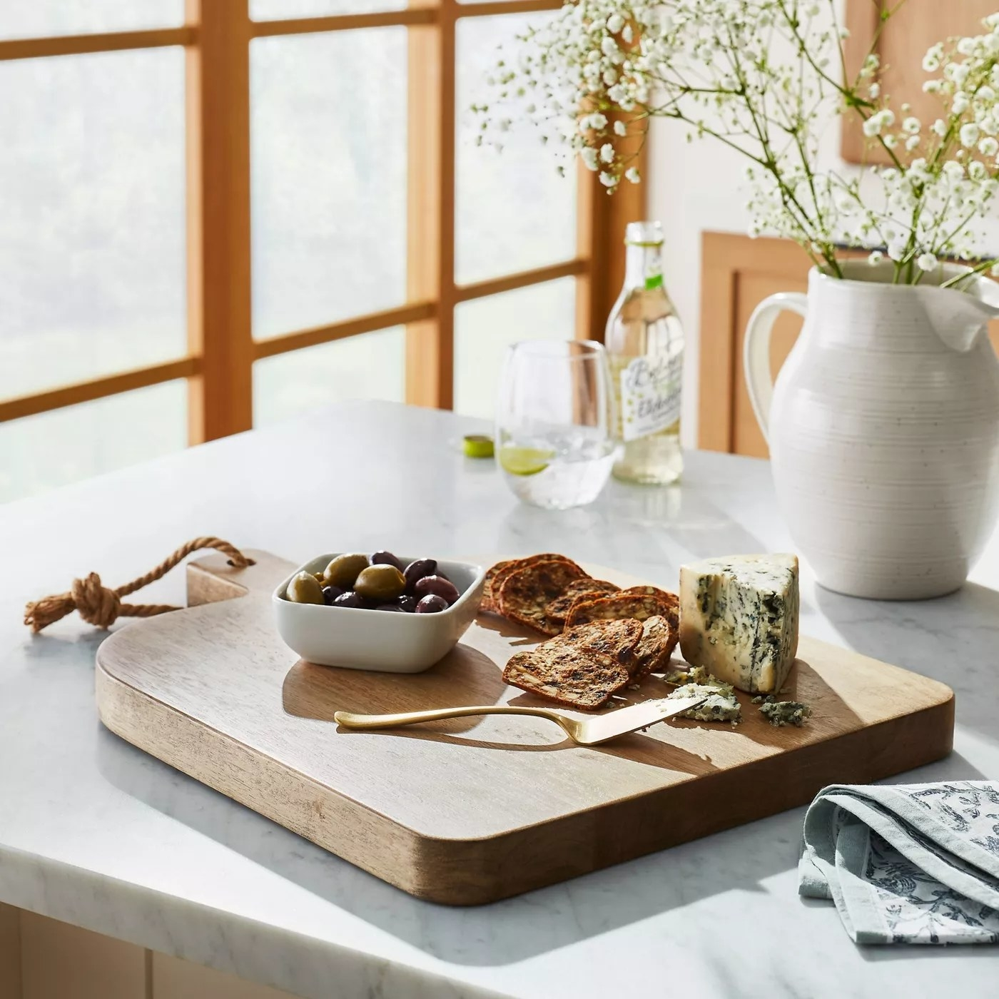 The board placed on a dining table with hors d'oeuvres on top