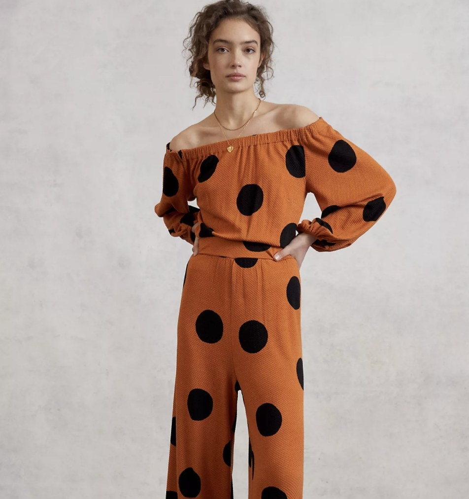 Model is wearing an orange jumpsuit with black circles