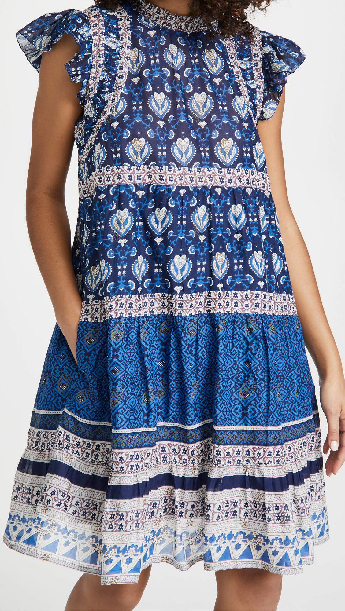 Model wearing the sleeveless, knee-length, ruffle trim dress in a blue print