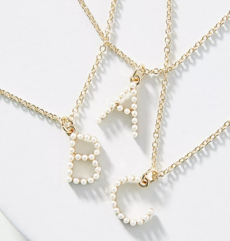 Three gold monogrammed necklaces