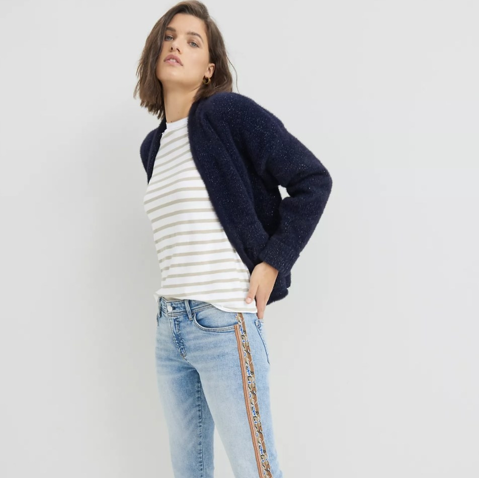 Model is wearing a dark blue cardigan, striped top, and denim pants