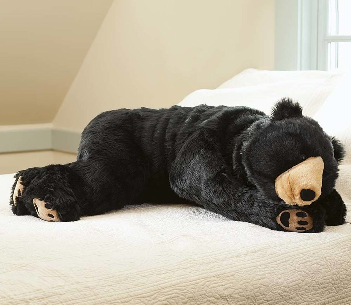 the black bear plush cuddle body pillow on a bed