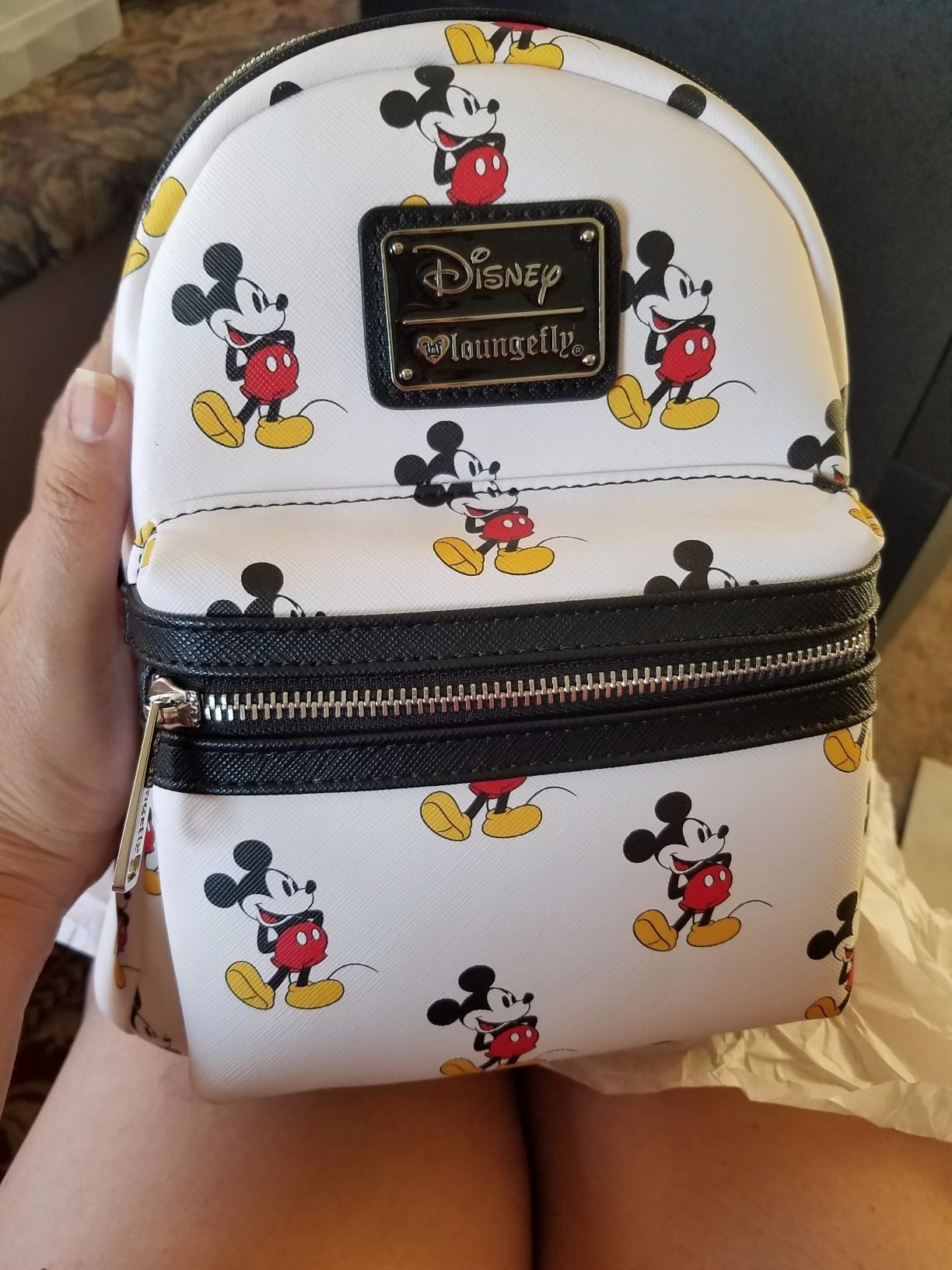 a white backpack with mickey mouse all over it