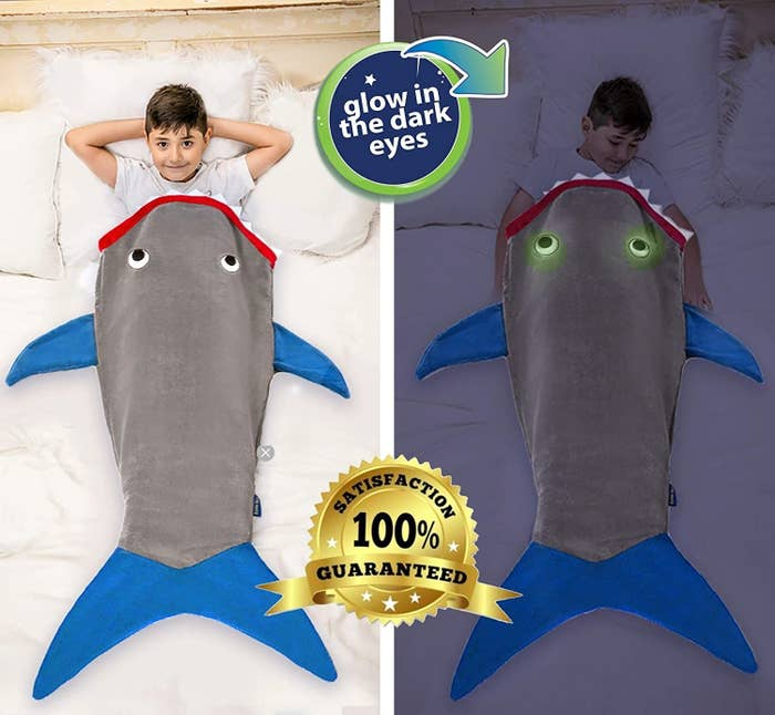 kid slipped into the shark blanket in the light, then in the dark showing its eyes glow in the dark