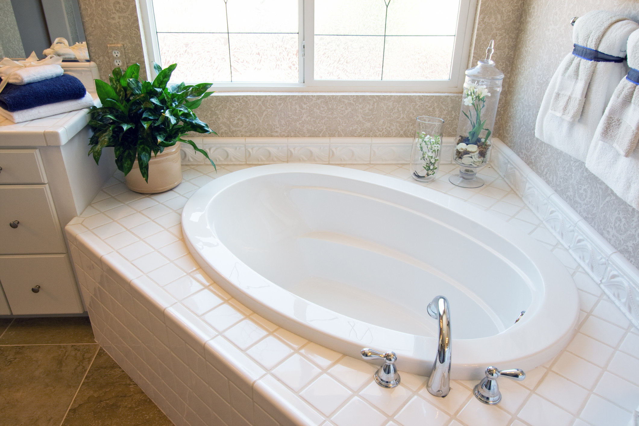 A large bath tub in the corner covered with white tile