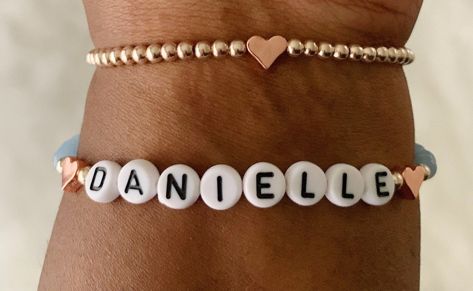 a gold beaded bracelet with rose gold hearts and a beaded name bracelet