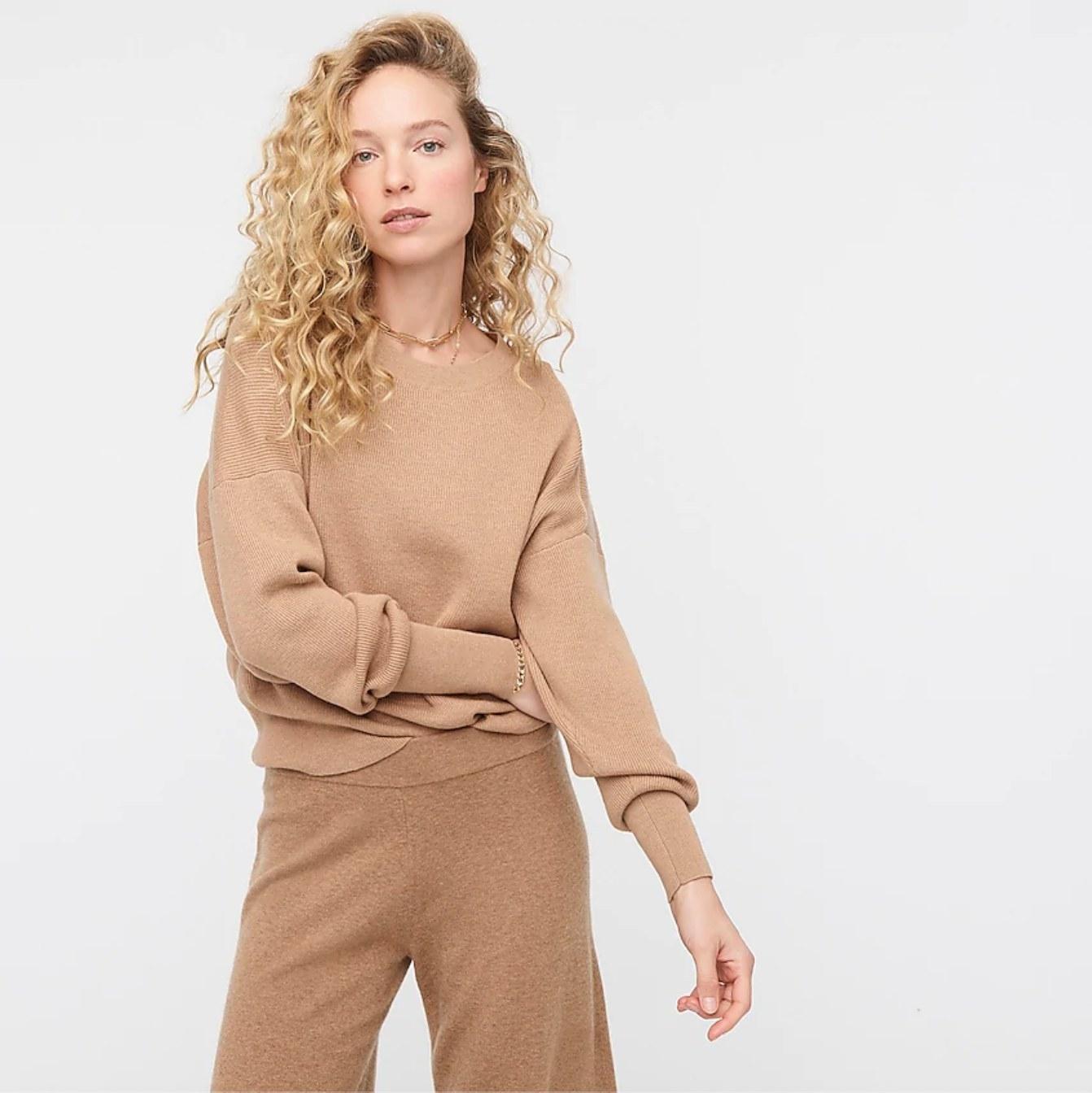model in the tan sweater