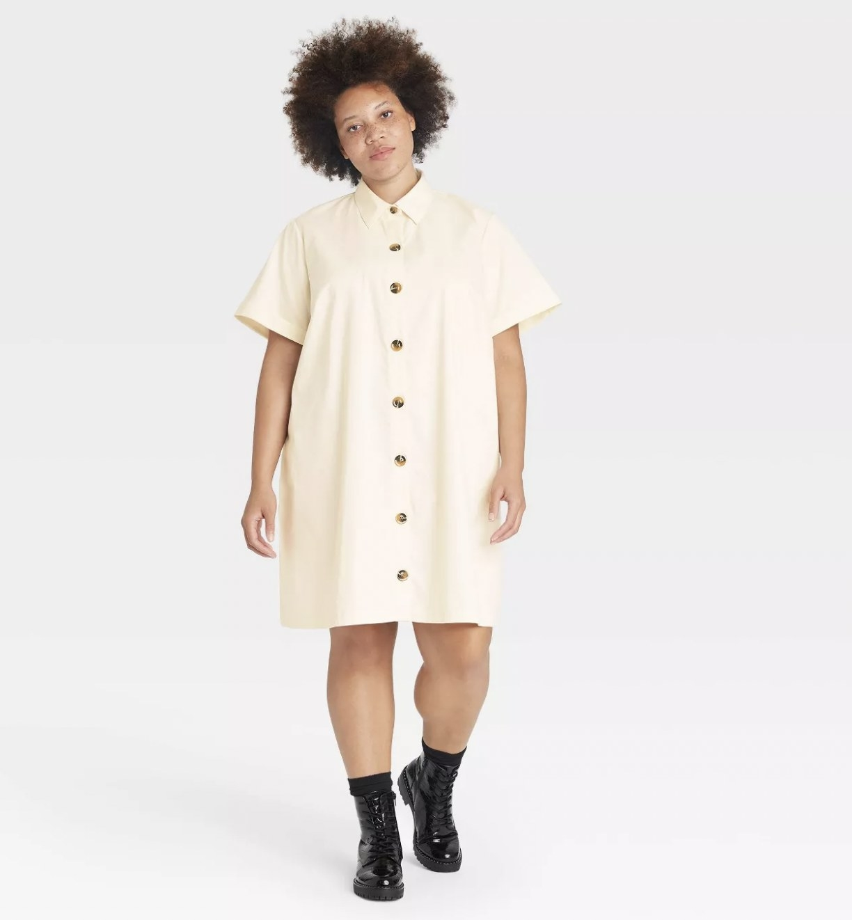 A model wearing a cream shirtdress with cuffed cap sleeves