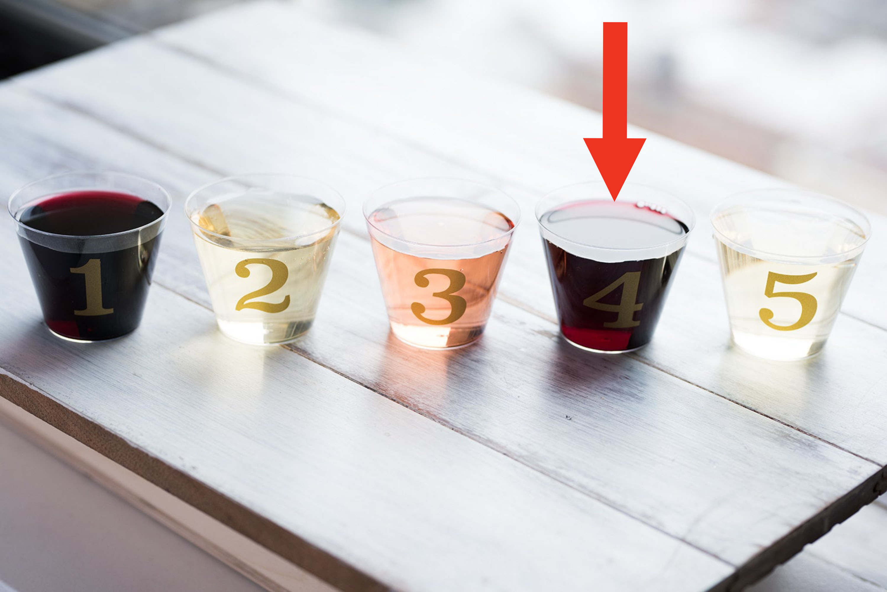 Several alcoholic beverages next to each other, with an arrow pointing at the red wine