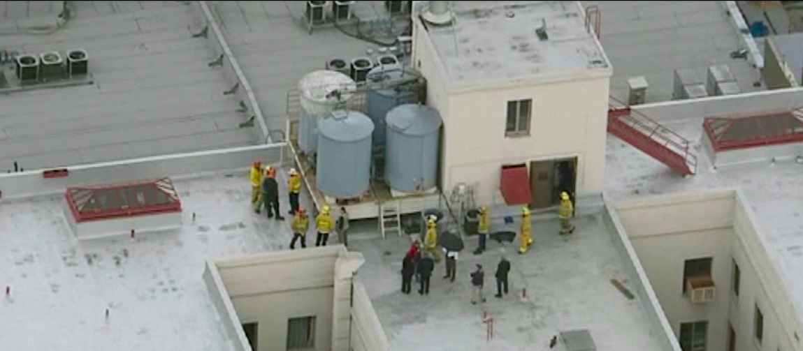 An aerial view of firefighters on a rooftop surrounding water tanks