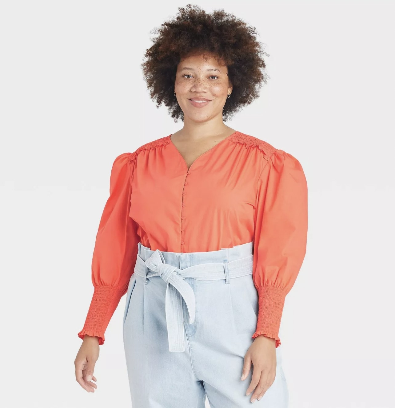 A model wearing an orange, V-neck cotton shirt with puffed sleeves