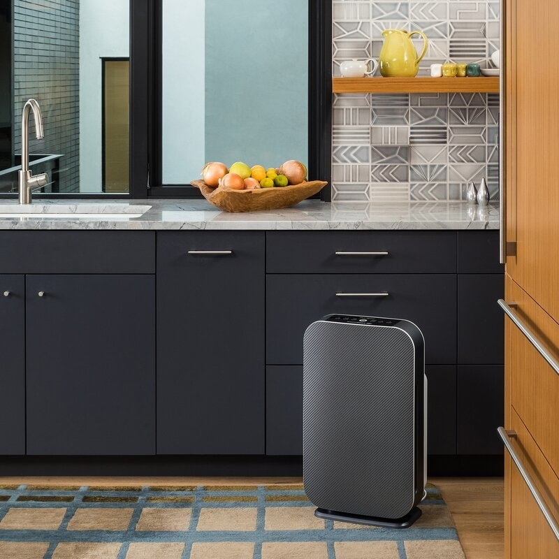 a black air purifier in front of a kitchen coutner