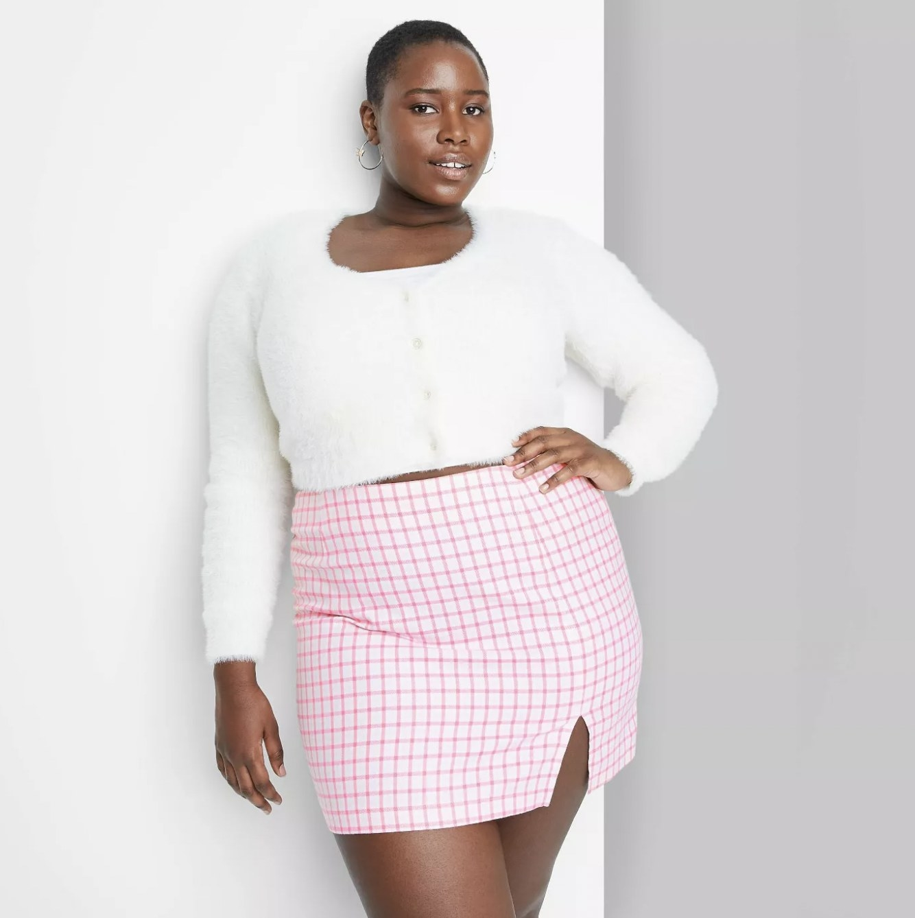 A model wearing a white buttoned sweater and a pink striped print skirt