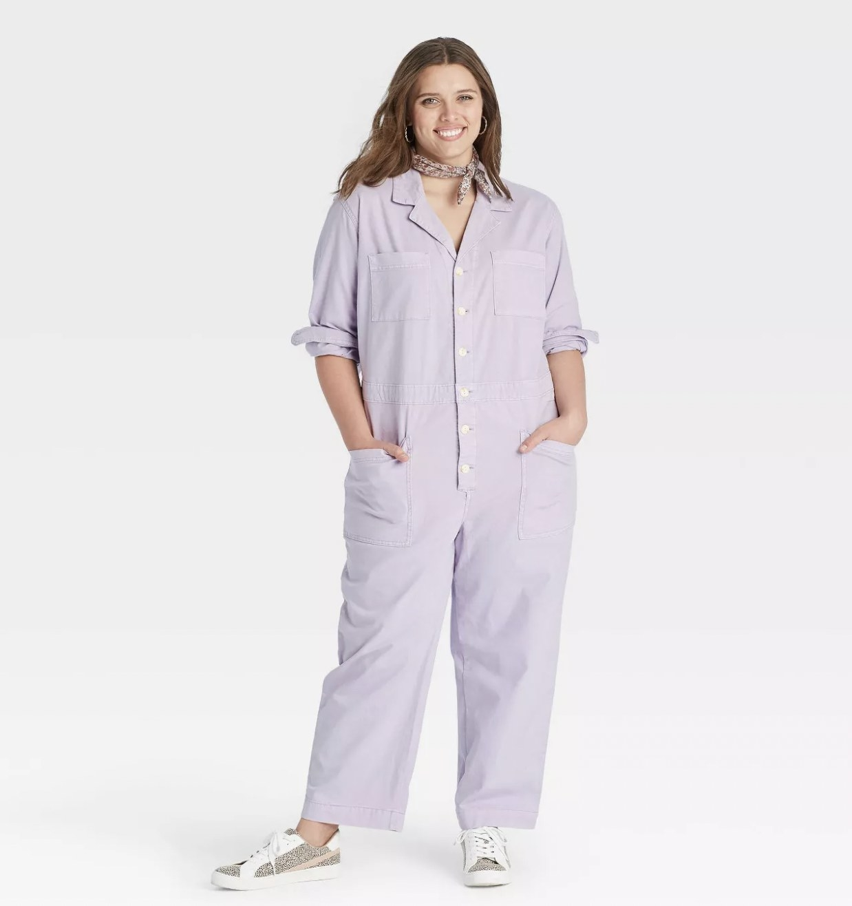 A model wearing purple loose-fitting coveralls with sneakers